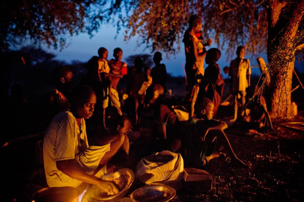 Women and their children who have been displaced by ongoing fighting camp outside in the open air. Kate Holt.