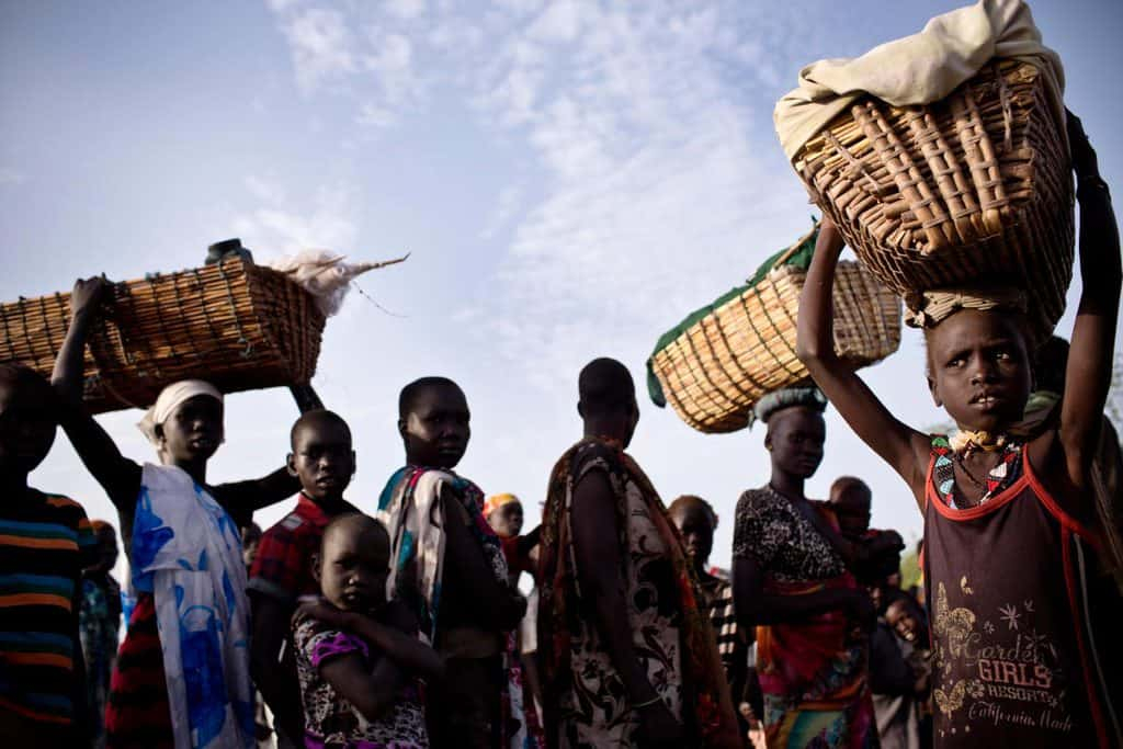 A young girl, who has been displaced by ongoing fighting carries her baby sister on her head in a basket. Kate Holt.