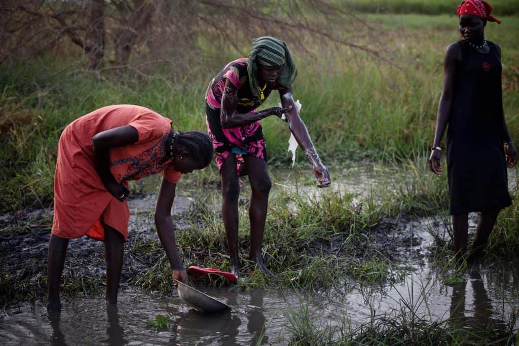 Two woman wash in swamp water while another collects water in a plastic container in a swamp. Kate Holt.
