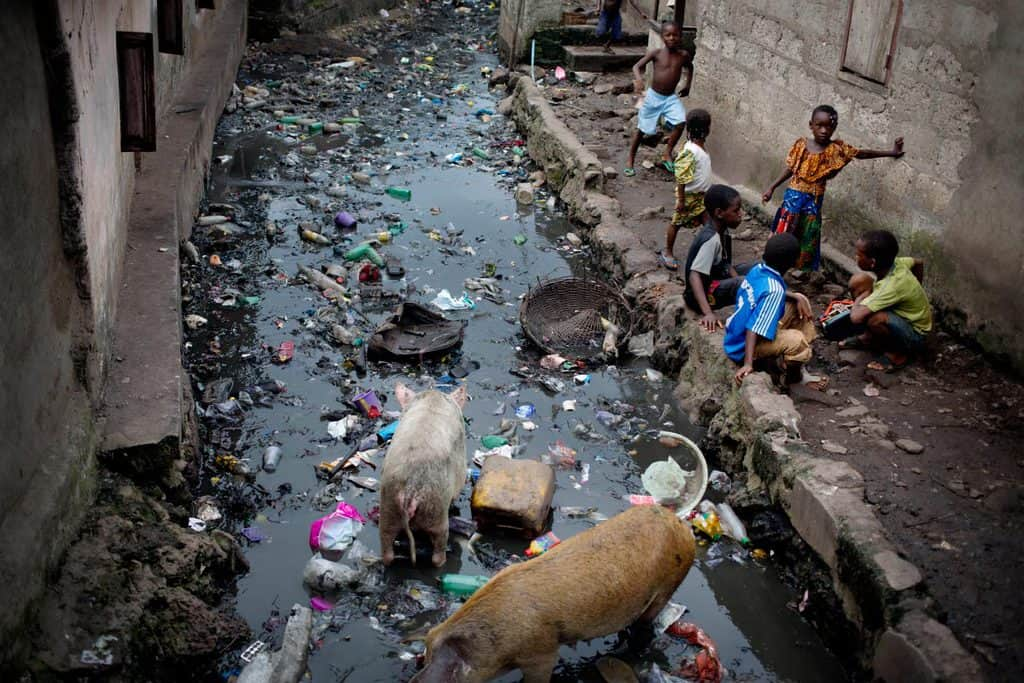 Children play beside a waterway that is choked with rubbish in the Magazine Wharf area of  Freetown, Sierra Leone. Kate Holt.