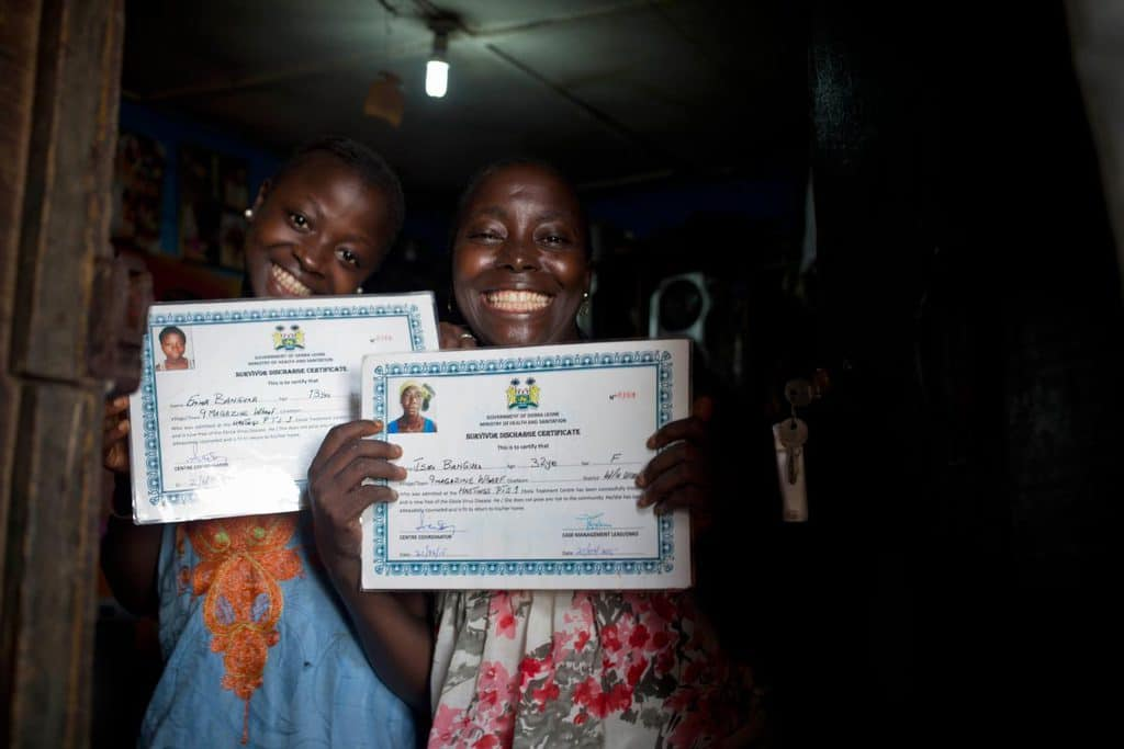 Isatu B (R) who is 33,  and her younger cousin Emma, who is 13,  pose for a photograph with certificates. Kate Holt.