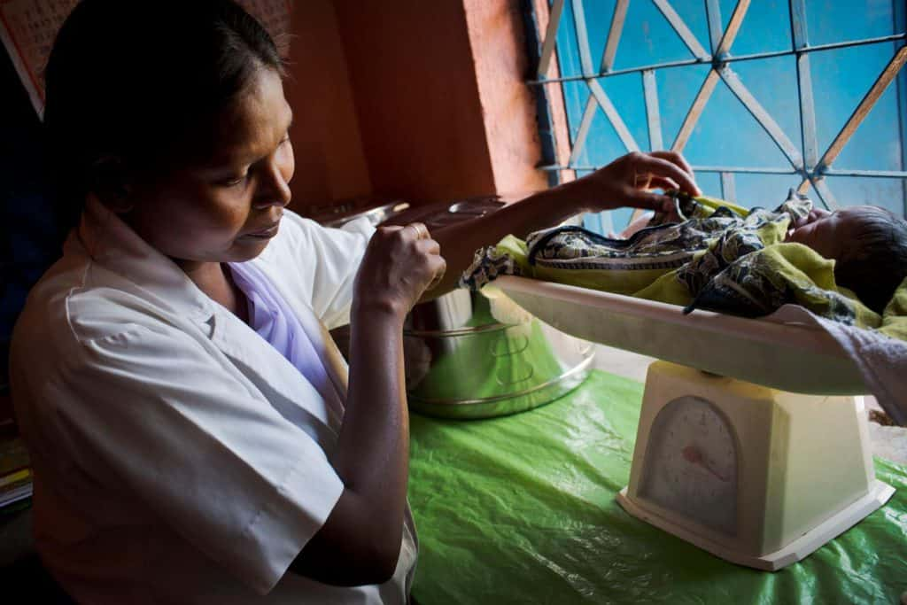 A health worker weighs a new born baby in Kolibera health centre near to Ranchi, India Friday, May 30, 2014. Kate Holt.