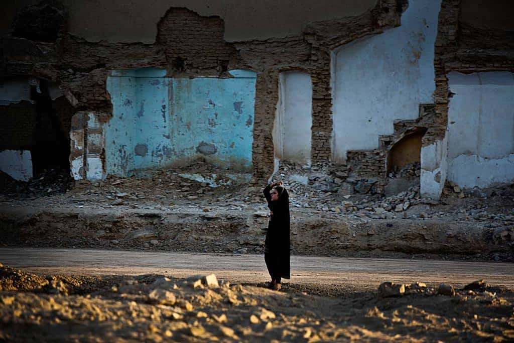 A woman walks past a destroyed building in Kandahar. Kate Holt.