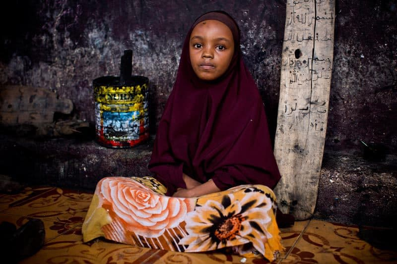 A young girl poses for a photo next to her Islamic script tablet in a Madrassa near the seaport in Mogadishu Somalia, on the 29th May, 2013