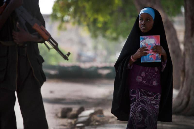 A young girl looks upped at an armed man in downtown Mogadishu, Somalia on the 11th July, 2012. Increasing numbers of violent and sexual attacks are being reported throughout the city, particularly in camps for displaced people.